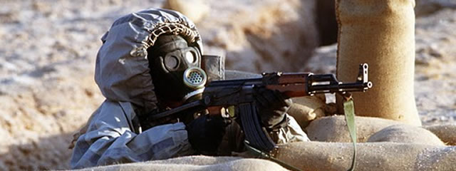 Syrian soldier in a Soviet-made Model ShMS nuclear-biological-chemical warfare mask aims an AK-47 assault rifle (picture Vir Vikram Singh)